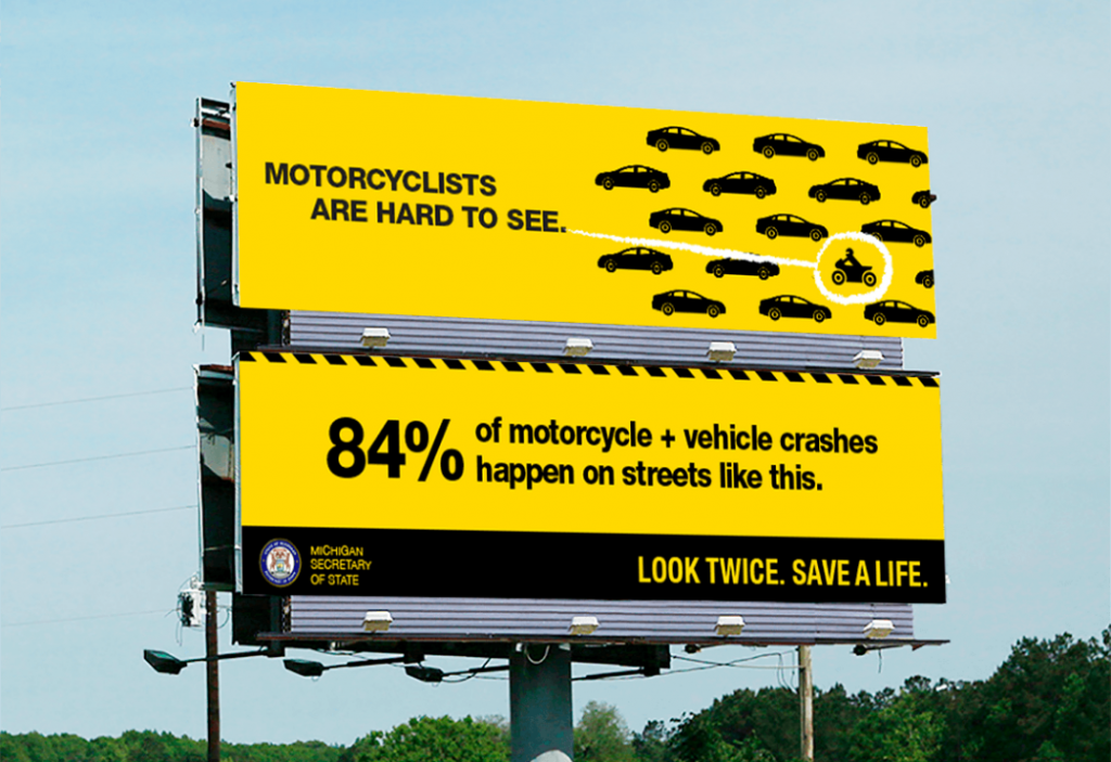 """Two billboards stacked, one on top of the other. The top board shows several illustrated cars with a single motorcyclist. The text reads, """"Motorcyclists are hard to see."""" The bottom board reads, """"84% of motorcycle and vehicle crashes happen on streets like this. Look twice. Save a life."""""""