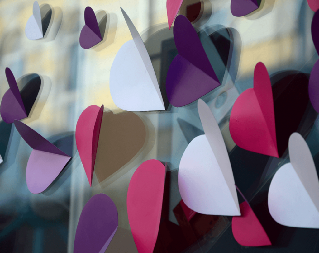 Several purple, red, and white cut paper hearts on a window.