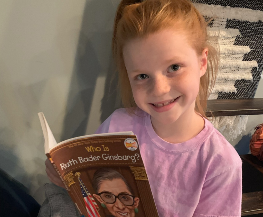 "Smiling young girl with red hair and freckles, holding a book titled, ""Who is Ruth Bader Ginsburg?"""