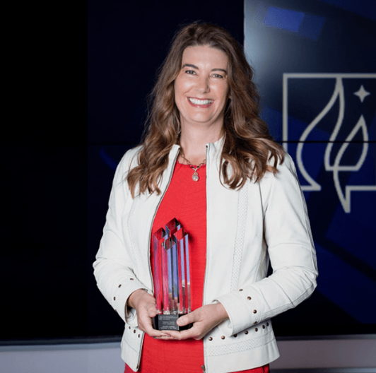 """Deb Horak holding a glass """"Business of the Year"""" award trophy."""